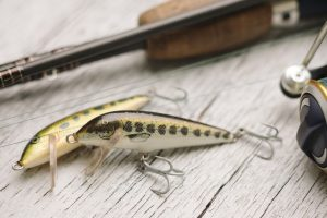 Close-up of fishing lures with rod on wooden background.